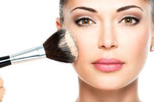 woman applying makeup with brush