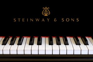Steinway & Sons logo close up. Classic gold lettering above the piano keys of a ebony black Steinway grand piano